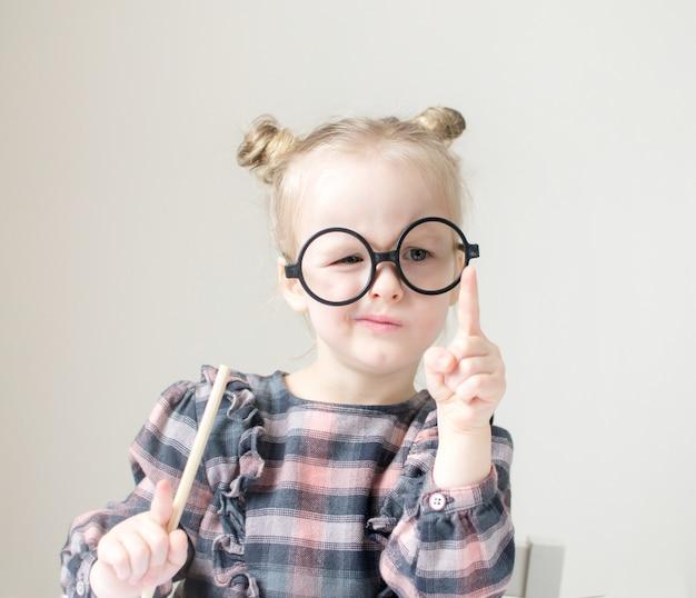 Kaukasisches kleines mädchen mit runden gläsern. kleiner lehrer. lustiger brillen-humor. retro-stil
