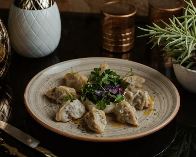 Kaukasisches köstliches lebensmittel khinkali, khingal fein gekocht und mit frischer petersilie und roten basilikablättern gedient