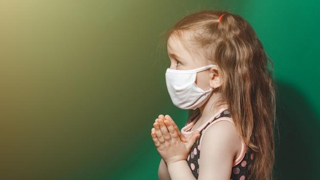 Kaukasisches krankes kleines mädchen in der medizinischen maske während der coronavirus-epidemie betet auf grünem hintergrund nahaufnahme 2021.kopierraum.