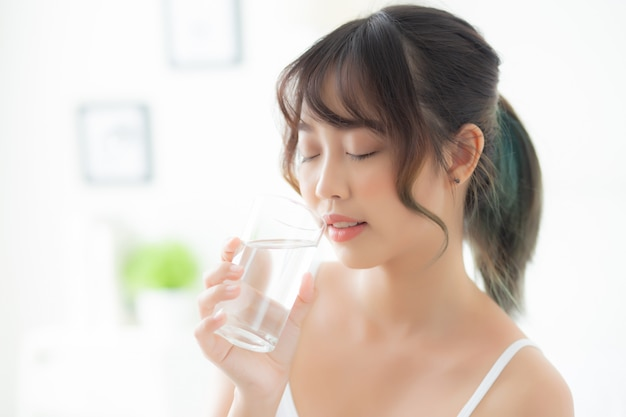 Kaukasisches lächeln der jungen asiatischen frau des schönen porträts mit der nahrung durstig und trinkglas wasser