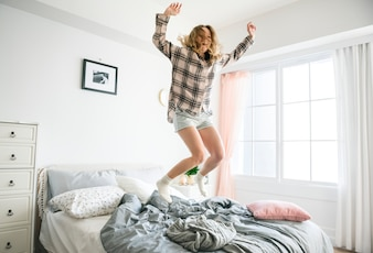 Kaukasisches Mädchen, das auf Bett springt