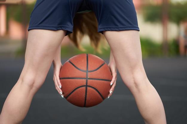 Kaukasisches mädchen, das ball zwischen beinen während eines straßenbasketballspiels gericht am im freien hält