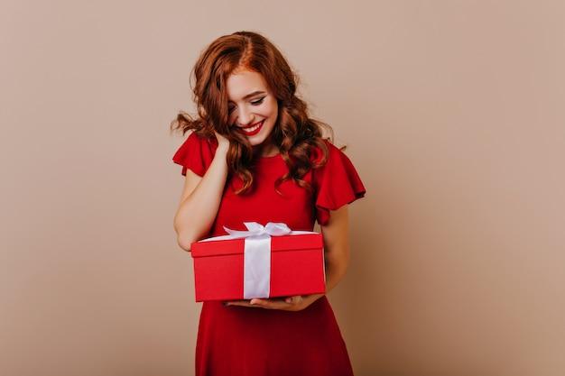 Kaukasisches mädchen, das geburtstagsgeschenk mit lächeln betrachtet. charmante ingwerdame, die neujahrsgeschenk hält.