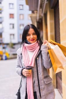 Kaukasisches mädchen, das in der stadt mit papiertüten und einem kaffee zum mitnehmen einkauft