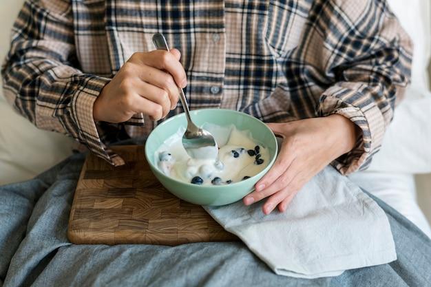 Kaukasisches mädchen, das joghurt auf bett isst
