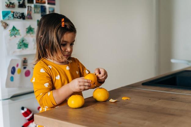 Kaukasisches mädchen, das mandarinen auf küchentheke schält. gesunde kinderernährung. immunverstärkung mit vitamin c. hochwertiges foto