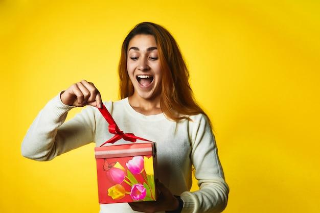 Kaukasisches mädchen der aufgeregten rothaarigen öffnet geschenk mit überraschtem gesicht