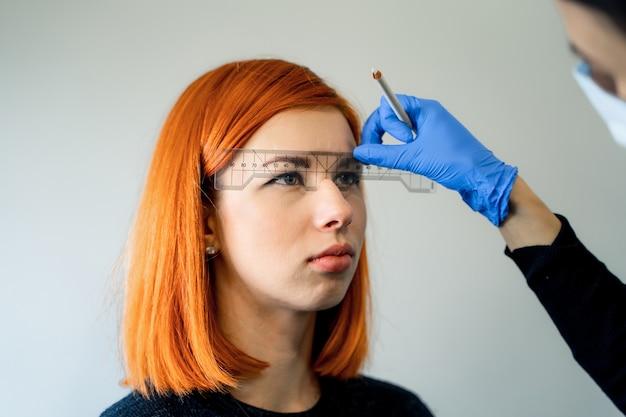 Kaukasisches mädchen der jungen kosmetikerin hält vorbildliche augenbrauenkorrektur. kosmetikerin bei der arbeit ist der arbeitsplatz eines augenbrauenspezialisten. augenbrauenkorrektur und färbeverfahren. schönheitsindustrie. lebensstil