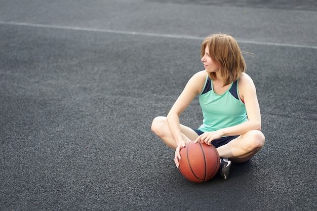 Kaukasisches mädchen der rothaarigen, das auf straßenbasketballplatz sitzt und eine kugel anhält