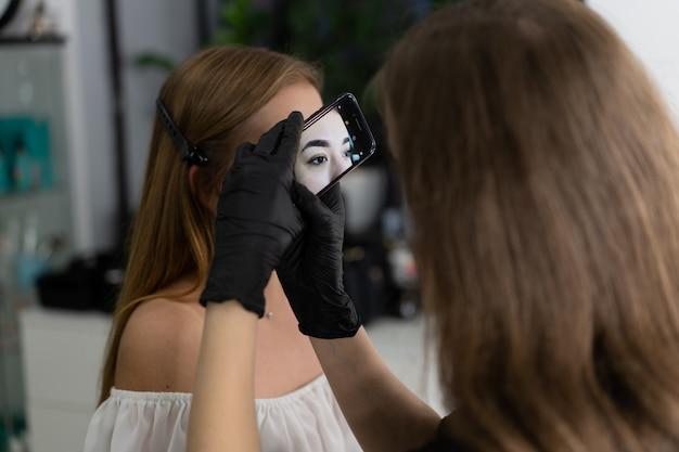 Kaukasisches mädchen des jungen kosmetikers hält vorbildliche augenbrauenkorrektur