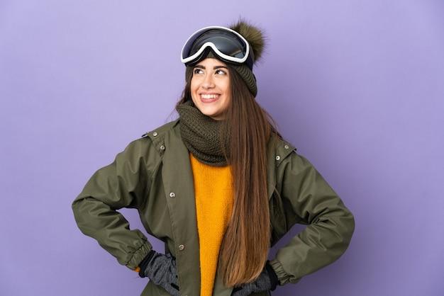 Kaukasisches mädchen des skifahrers mit snowboardbrille lokalisiert auf lila wand, die mit armen an der hüfte aufwirft und lächelt