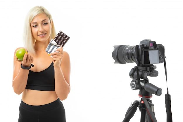 Kaukasisches mädchen des sports zeigt schokolade und grünen apfel vor kamera, das lokalisierte porträt