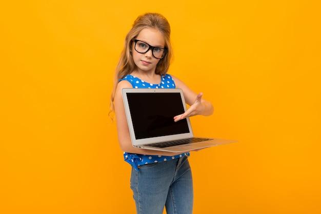 Kaukasisches mädchen hält laptop-bildschirm vorwärts auf einer orange wand