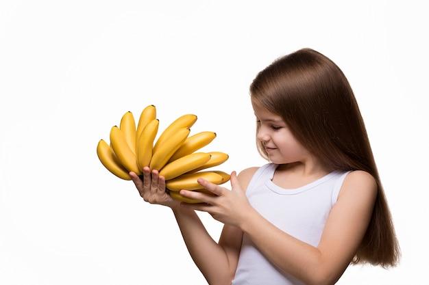 Kaukasisches mädchen im weißen laptop, der bananen hält