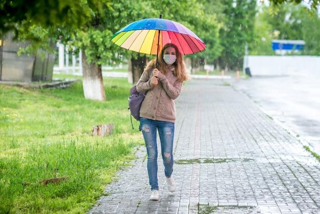 Kaukasisches mädchen in der schutzmaske geht unter einem regenschirm auf leerer straße im frühlingsregen. sicherheit und soziale distanz