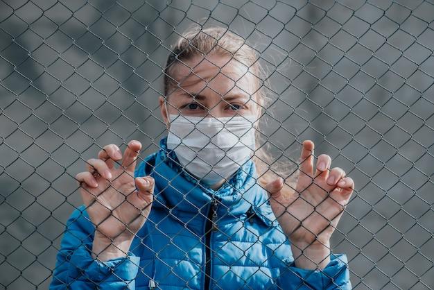 Kaukasisches mädchen in einer medizinischen schutzmaske steht hinter einem metallzaun und sieht traurig aus. strenge hausisolation während der quarantäne.