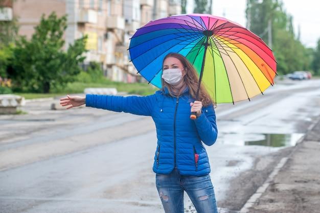 Kaukasisches mädchen in einer schutzmaske begrüßt taxi auf einer leeren straße, steht mit einem regenschirm im frühlingsregen und wartet auf auto. sicherheit und soziale distanz