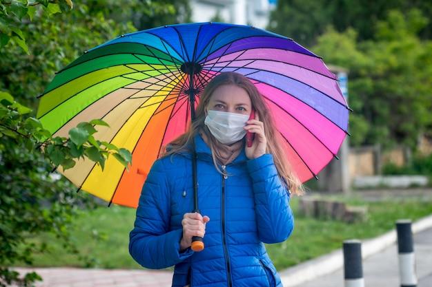 Kaukasisches mädchen in einer schutzmaske steht auf einer leeren straße an einer bushaltestelle unter einem regenschirm im frühlingsregen und spricht am telefon.