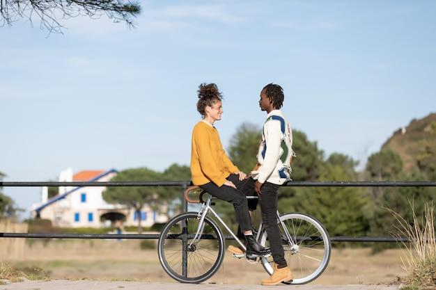 Kaukasisches mädchen mit afrikanischem jungen auf dem gleichen fahrrad mit einem park mit bäumen. interracial konzept
