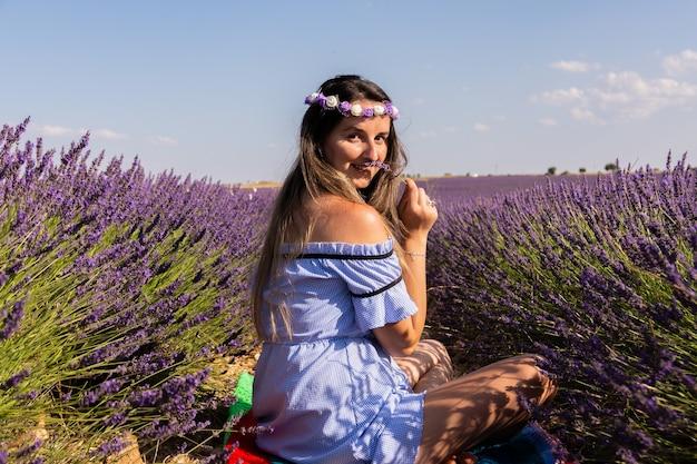 Kaukasisches mädchen mit einem blauen kleid und kranz, die auf lavendelfeldern sitzen.