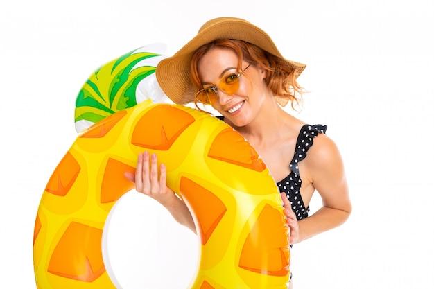 Kaukasisches mädchen mit einem schönen lächeln in einem retro-badeanzug und einem strohhut hält einen schwimmkreis in form von ananas auf einer weißen wand
