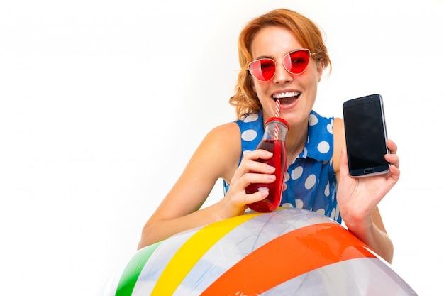 Kaukasisches mädchen mit einem telefon mit einem modell und einem glas getränk an einer weißen wand