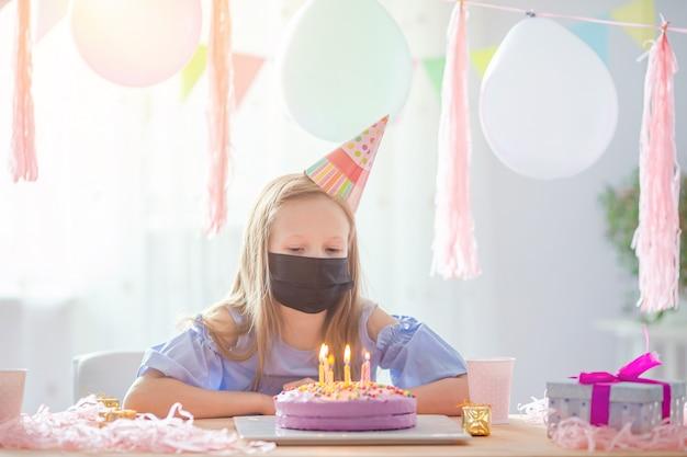 Kaukasisches mädchen tragen eine maske an ihrem geburtstag. festlicher bunter hintergrund mit luftballons. geburtstagsfeier und wunschkonzept.