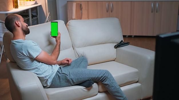 Kaukasisches männlich aussehendes telefon mit mock-up-chroma-key-display mit grünem bildschirm