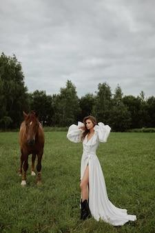Kaukasisches modellmädchen mit perfektem schlanken körper im langen weißen kleid, das mit einem braunen pferd auf der grünen sommerwiese aufwirft