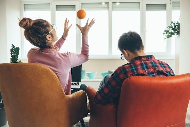 Kaukasisches paar, das im sessel sitzt und laptop beim spielen mit einer orange benutzt