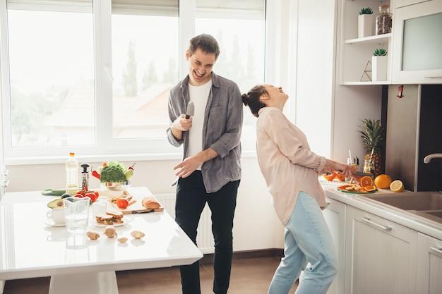 Kaukasisches paar, das in der küche zusammen kocht und lächelt, das spielt und früchte schneidet