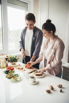 Kaukasisches paar, das produkte beim zubereiten von sandwiches mit einem lächeln in der küche schneidet