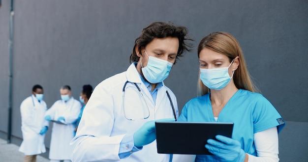 Kaukasisches paar mann und frau, ärztekollegen in medizinischen masken arbeiten und tablet-gerät verwenden. menschen im hintergrund. männliche und weibliche ärzte tippen und scrollen auf dem gadget-computer.