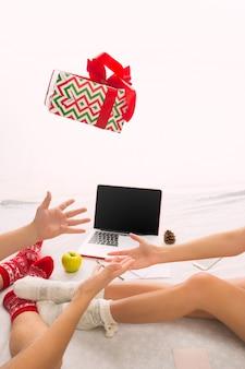 Kaukasisches paar mit geschenk. laptop und telefon für leute, die auf dem boden an farbigen socken sitzen. weihnachten, liebe, lifestyle-konzept