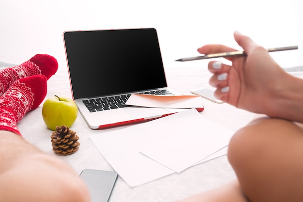 Kaukasisches paar zu hause mit internet-technologie. laptop und telefon für leute, die auf dem boden an farbigen socken sitzen.