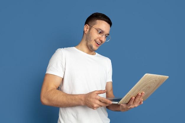 Kaukasisches porträt des jungen mannes auf blau