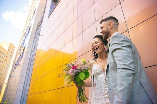 Kaukasisches romantisches junges paar, das die ehe in der stadt feiert. zarte braut und bräutigam auf der straße der modernen stadt. familie, beziehung, liebeskonzept