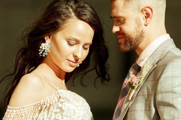 Kaukasisches romantisches junges paar, das ihre ehe in der stadt feiert. zarte braut und bräutigam auf der modernen stadtstraße am sommertag. familie, beziehung, liebeskonzept. zeitgenössische hochzeit. zuversichtlich.