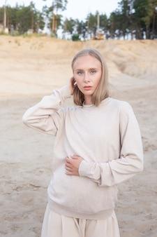 Kaukasisches schönes junges mädchen mit langen haaren und nacktem make-up in beige kleidung wirft draußen auf sand vor wald auf