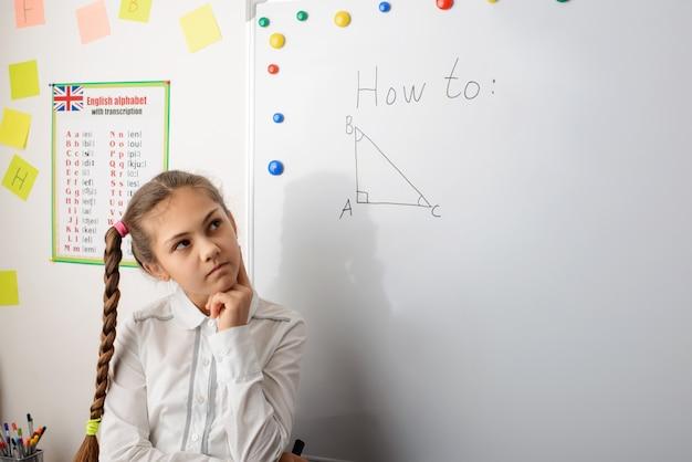 Kaukasisches schulmädchen, das über die mathematische übungsaufgabe nahe der tafel nachdenkt
