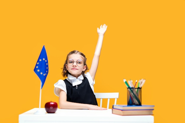 Kaukasisches schulmädchen, das während des unterrichts englischunterricht europa-flagge am schreibtisch die hand erhebt