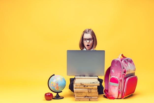Kaukasisches schulmädchen unter schock, das hinter einem stapel büchern sitzt und sich die bildung von laptop-kindern ansieht