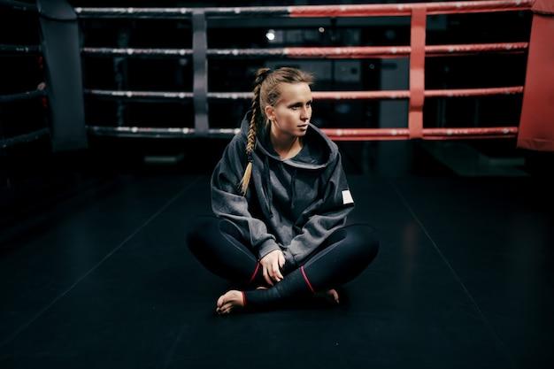 Kaukasisches starkes boxermädchen, das im ring im sweatshirt und mit verband auf füßen sitzt und wegschaut.