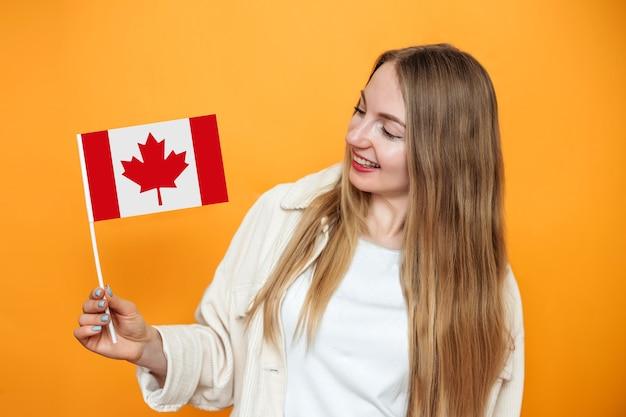 Kaukasisches studentenmädchen lächelt und hält eine kleine kanada-flagge und schaut auf die kamera einzeln auf orangem hintergrund, kanada-tag, urlaub, konföderationsjubiläum, kopierraum