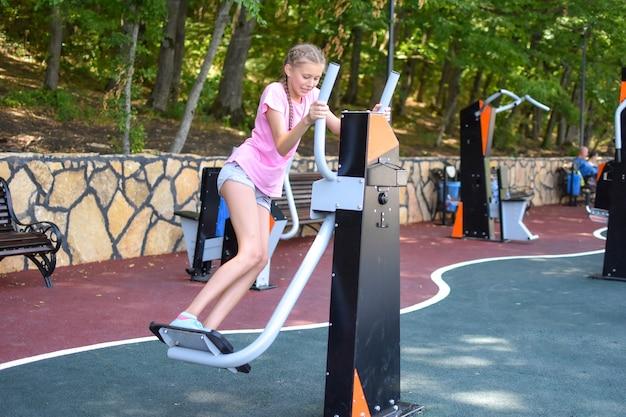 Kaukasisches teenager-mädchen auf spielplatz im freien. kindersport für die gesundheit.