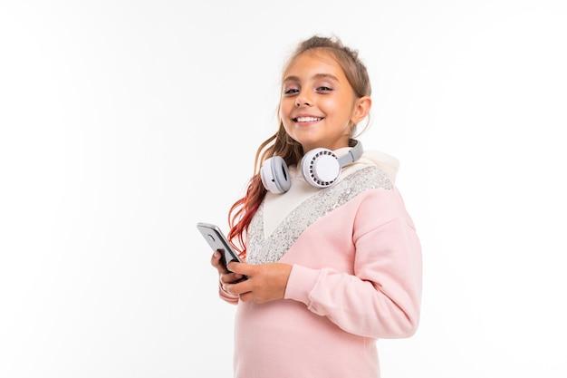 Kaukasisches teenager-mädchen im rosa kapuzenpulli kommuniziert mit freunden oder familie, schaut film oder karikatur, porträt lokalisiert auf weißem hintergrund