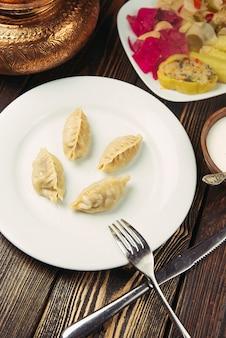 Kaukasisches traditionelles essen, khinkali, dushbere, gurze, serviert mit turshu.