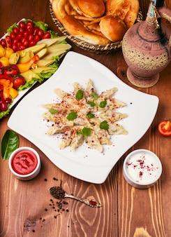 Kaukasisches traditionelles foodl dushbere, gurze diente mit joghurt und tomatensauce. in weißen teller mit turshu auf holztisch dekoriert