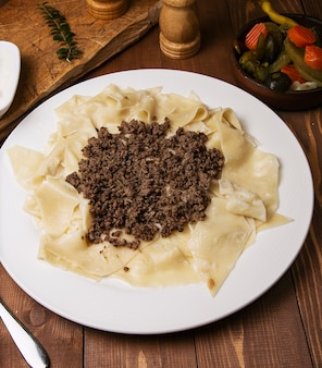 Kaukasisches traditionelles foor khingal, khinkali. kaukasische teigwaren mit fleisch in der weißen platte auf holztisch.