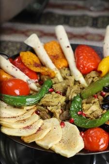 Kaukasisches traditionelles sac ici mit gebratener kartoffel, auberginenscheiben, tomaten, pfeffer und rindereintopf